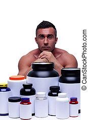Serious sportsman sitting at the table with sports nutrition