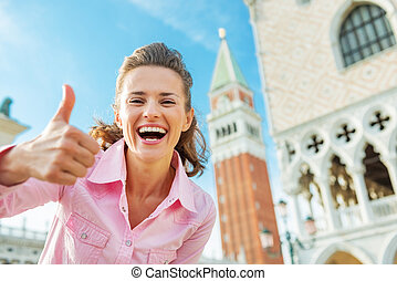 Happy young woman against campanile di san marco showing...
