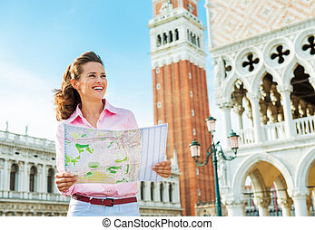 Happy young woman looking at map against campanile di san...