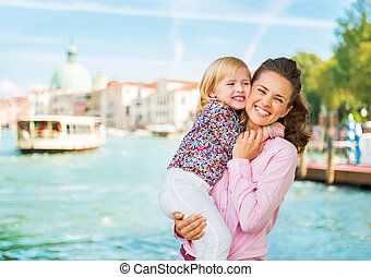 Portrait of happy mother and baby hugging on grand canal...