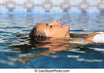 Profile of a beauty relaxed woman face floating in water of...