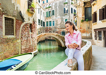 Happy young woman sitting on bridge in venice, italy and...