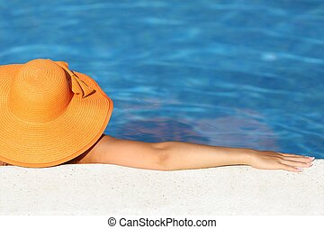 Woman with picture hat bathing relaxed in a pool enjoying...