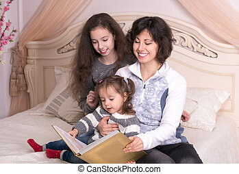 Mom reading a book with children Little girl holding a big...