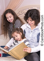 Mom reading a book with children.