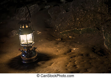 The old antique storm lantern in a cave