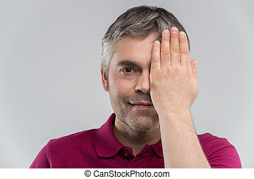 Closeup portrait of young man covering his eye. Portrait of confident adult man covering his eye with hand while isolated on grey