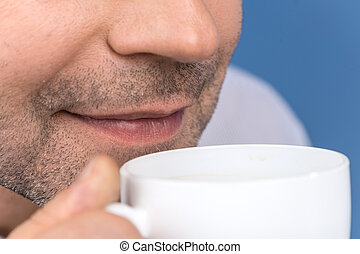 Happy adult man drinking coffee on blue. closeup on man enjoying cup of coffee with eyes closed
