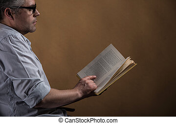 Man sitting in chair and reading book. profile of adult man...