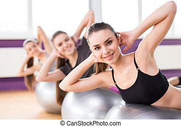 Fitness - Sporty women are doing sit-ups on the exercise...
