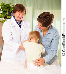 doctor examining baby at clinic office - Happy mature female...