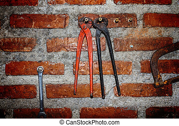 Pincers - Two pincers on the wall block background.