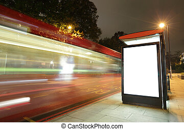 Blank billboard in bus stop at night with the lights of the...