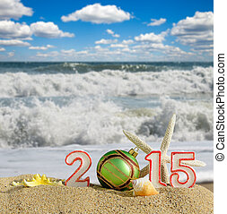 New year 2015 sign with seashells, starfish and christmas ball on a beach sand