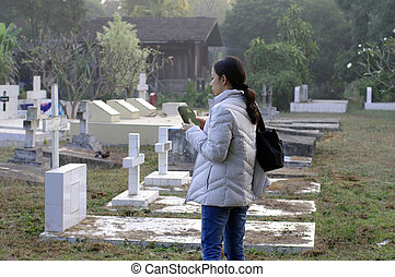 girl holding bible at cemetery - girl with jacket holding...