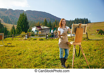 Young painter at work in the mountains with palette