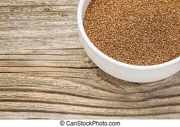 teff grain in bowl - a small ceramic bowl of gluten free...