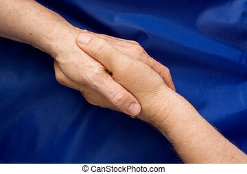 Commitment - Hand shake against a blue background