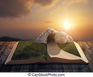 Empty grave - An open Bible with an empty tomb and stone on...