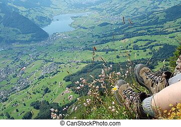 Hiking boots and flowers over a valley