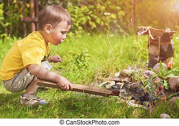 Caucasian Little Boy Dealing With Fire near Firepace...