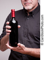 bottle of red wine and hands of a man - a senior expert...