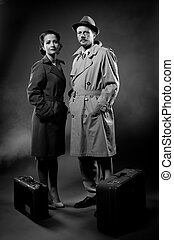 Film noir: elegant couple ready to leave with luggage...