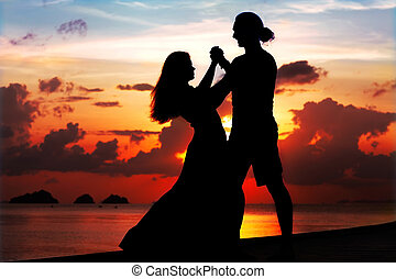 man and woman dancing smiling at sunset