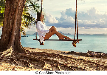 girl sitting on the swing near the palm trees on the beach