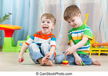 children boys with toys in playroom - children boys with...