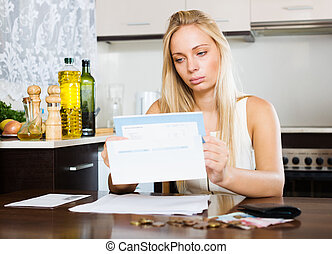 serious blonde girl with money and documents in home...