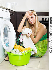 blonde girl and washing machine - Unhappy blonde girl using...