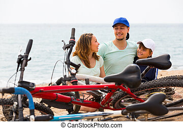 Family with bicycles on beach