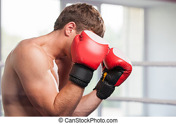 Handsome muscular young man wearing boxing gloves waist up...