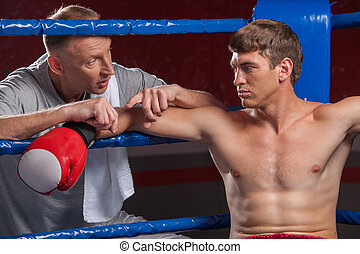 Senior coach advising boxer after end of round. two man in...