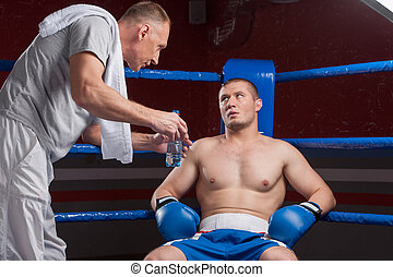 Senior coach advising boxer after end of round coach giving...