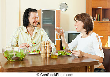 brunette woman with man eating veggie salad at home
