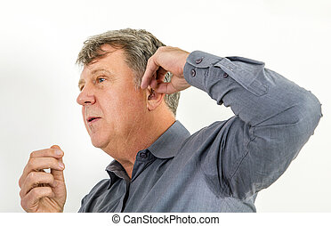 serious man in shirt handling his hearing aid - man with...