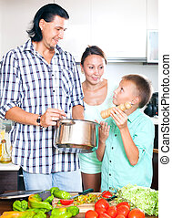 Happy family cooking veggie lunch - Happy man and woman with...