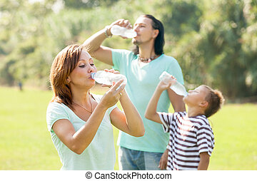 ordinary family of three drinking water from plastic bottles...