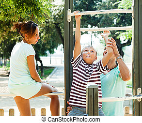 couple with son training with chin-up bar - adult couple...
