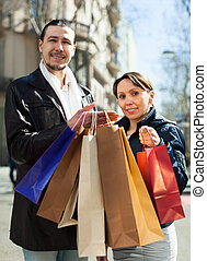 couple in black jackets with purchases