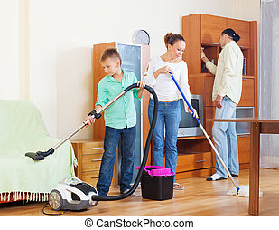 Family cleaning with vacuum cleaner - couple and teenager...