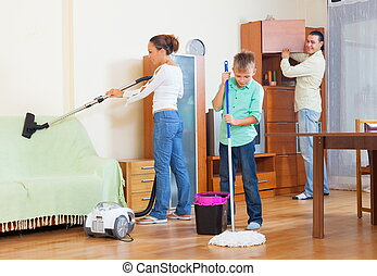 Couple with son vacuuming together - Middle-aged couple with...