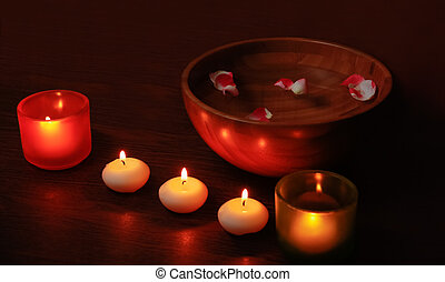 Glass candlesticks and candles and wooden bowl of water with...