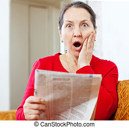 surprised woman with newspaper - Mature surprised woman with...