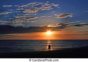 Romantic Sunset - A couple standing watching the beautiful...