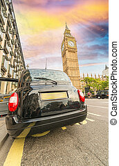 Black London cab under Big Ben tower and Westminster Palace.