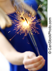 woman holding sparklers in her hand - woman holding sparkler...