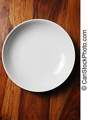 Empty white plate on wooden tabletop